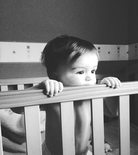 Cute boy in crib at home