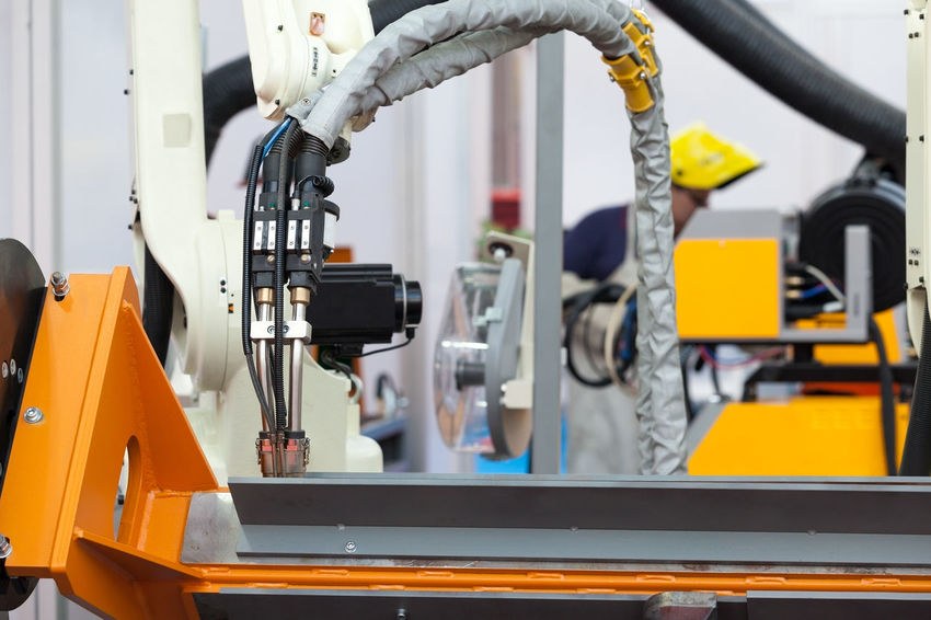 Industrial welding robot arm in the focus, blurred welder in the background Worker Industrial Industry Machine Machinery Production Welding Working Automated Automatic Equipment Factory Industrial Robot Manufacture Manufacturing Metal Operating Precision Robot Robotic Arm Speed Steel Technology Welder