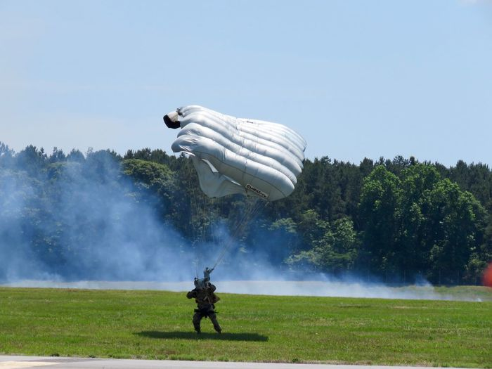 Military Soldier Landing On Lawn Field With Parachute Against Sky