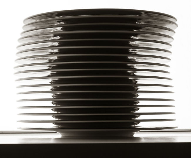 At The Restaurant Backlighting Close-up Day Indoors  No People Stack Of Plates Placed By The Window White Background