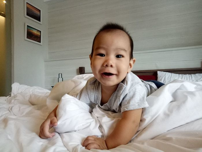Portrait Of Cute Baby Boy Relaxing On Bed At Home