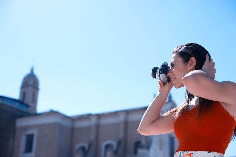 Low angle view of beautiful woman photographing by church against clear sky
