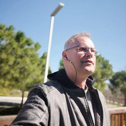 Mature Man Looking Away While Listening Music On Headphones