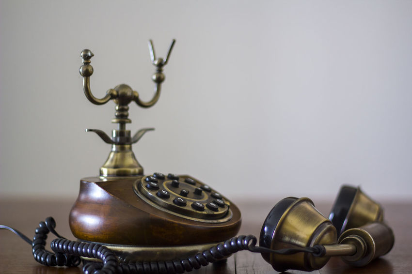 Vintage phone on wooden table with handset down Antiquated Antique Classic Copy Space Retro Antique Call Communication Connection Dial Handset History Landline Phone No People Number Old Old Telephone Phone Retro Styled Style Table Technology Telecommunications Equipment Telephone Vintage