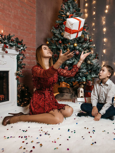 Woman sitting in christmas tree