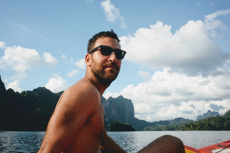Portrait of shirtless man kayaking on sea against sky
