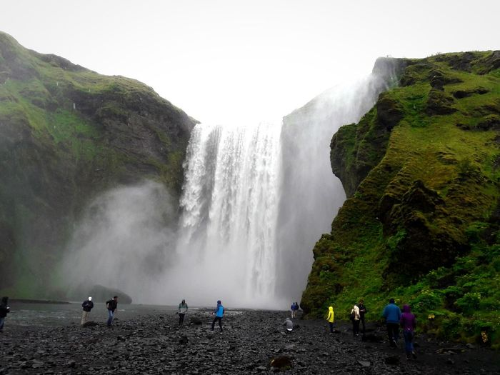 Tourists against waterfall