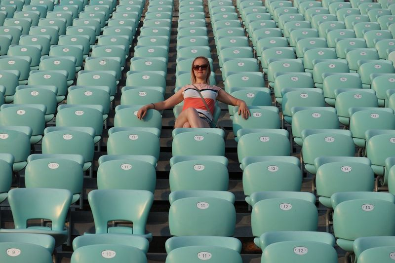 Low angle view of woman sitting on seat at stadium