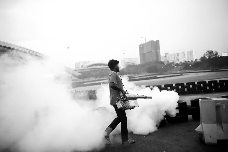 Full length of man holding mosquito fogging machinery against sky in city