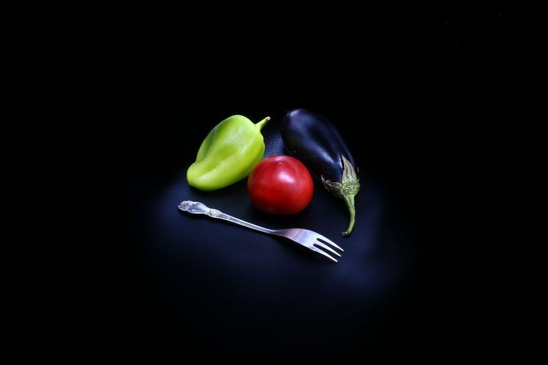 High angle view of vegetables with fork against black background