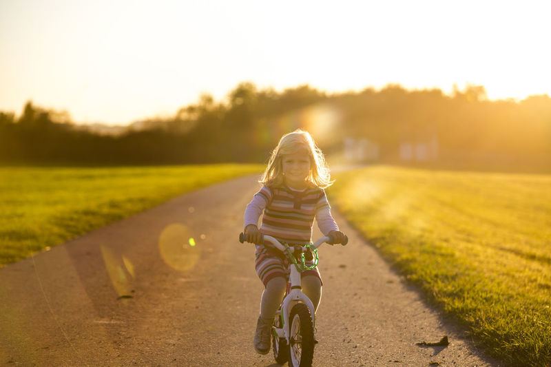 Girl riding bicycle on road amidst field during sunset