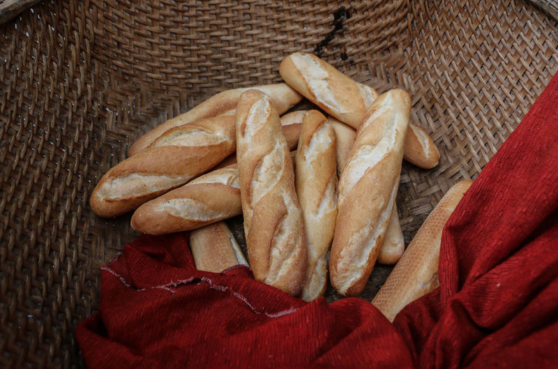 High angle view of baguettes with red fabric in wicker basket