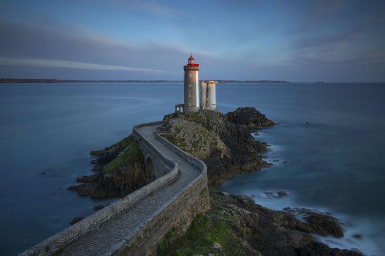 Lighthouse amidst sea against sky