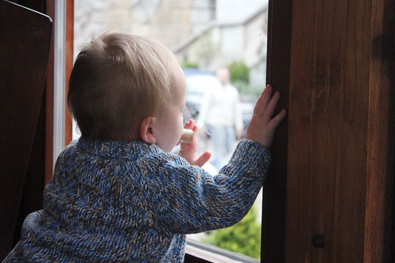 Rear View Of Baby Boy Looking Through Window At Home