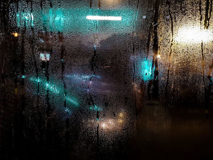 Illuminated lights seen through wet glass window at night