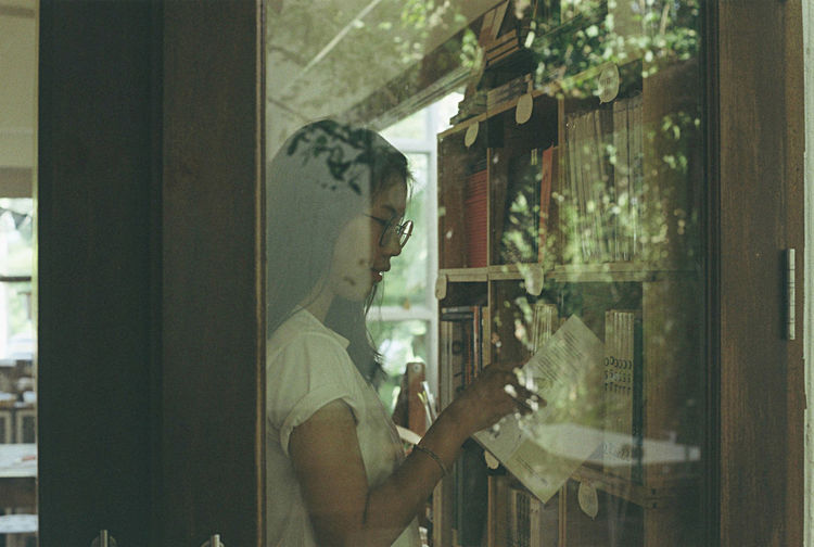 Woman taking book from bookshelf seen through window