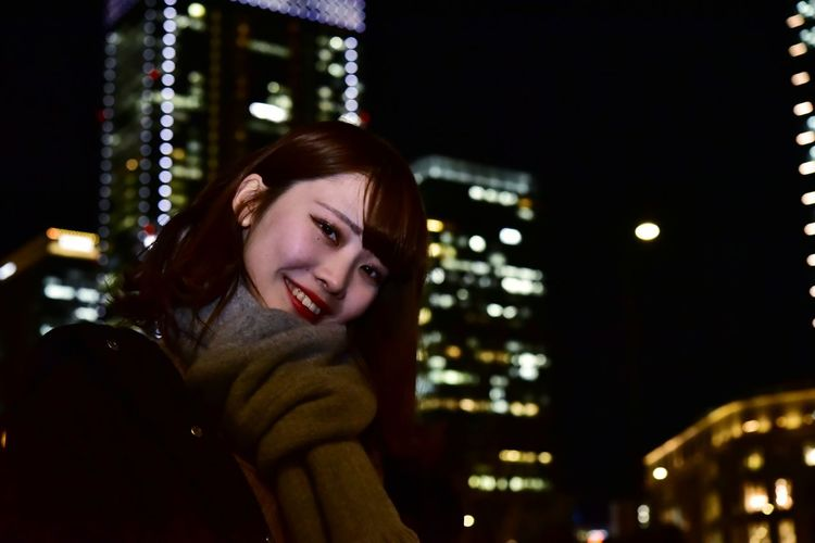 Portrait of smiling young woman in city at night