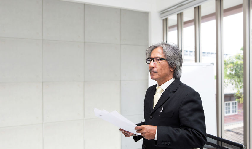 Businessman Holding Documents In Office