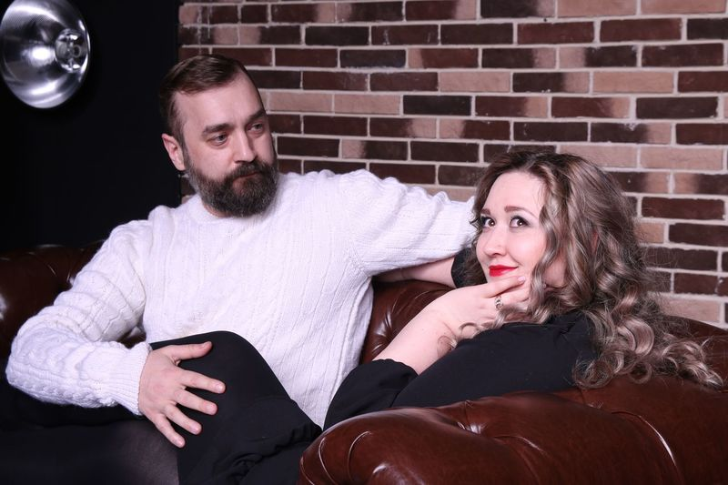 Man Looking At Thoughtful Woman Sitting On Sofa Against Brick Wall