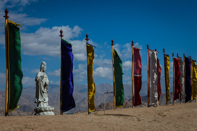 Low angle view of multi colored flags by statue on field against blue sky