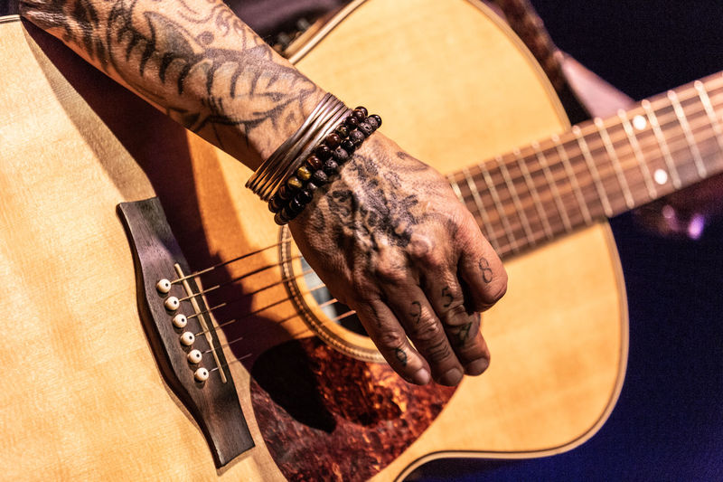Cropped image of tattooed hand playing guitar