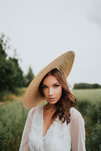 Portrait of beautiful young woman wearing hat against sky