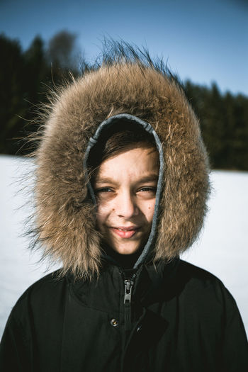 Portrait of smiling boy standing on snow field against sky