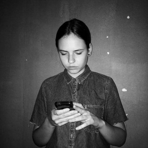 Young woman using mobile phone against wall