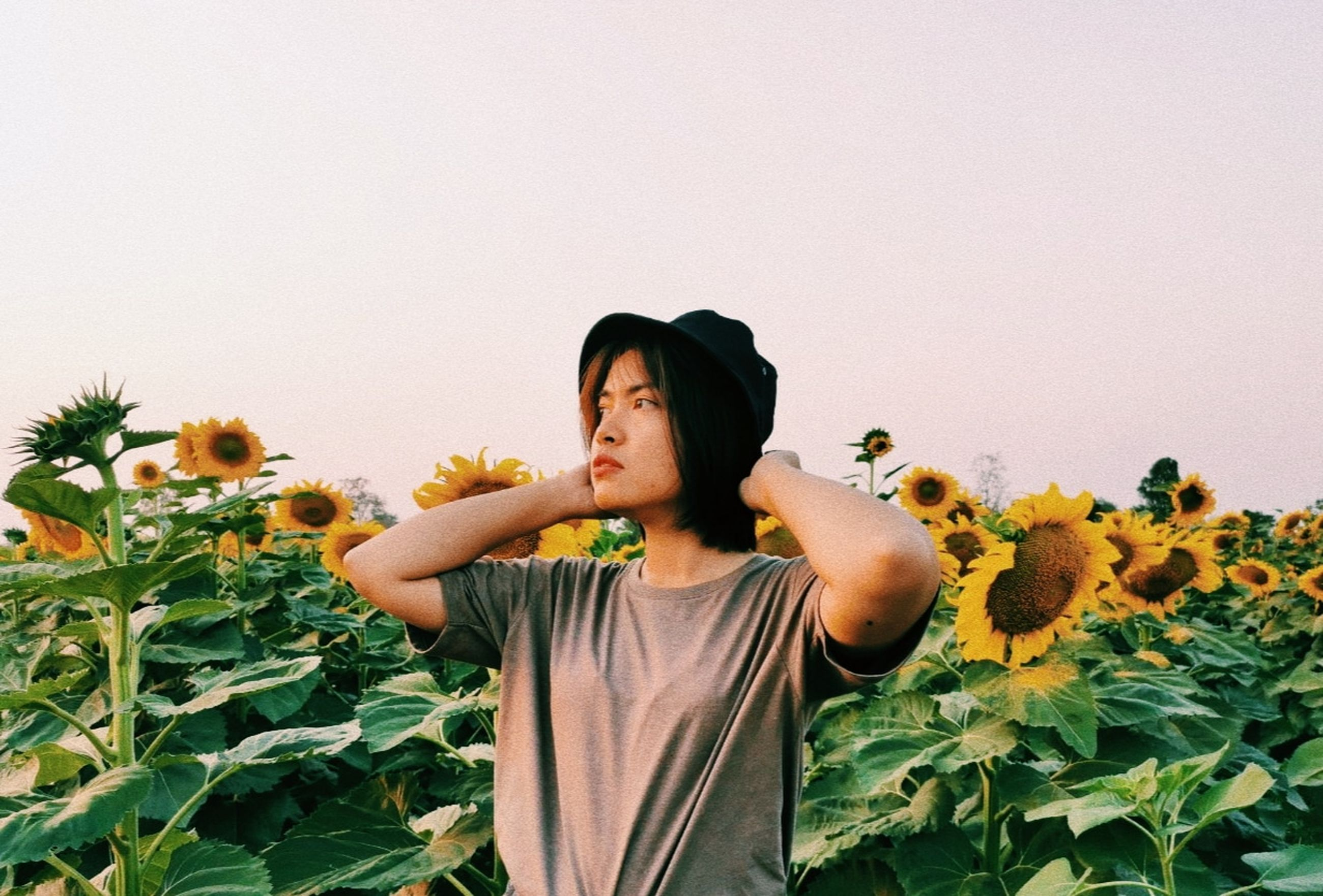 plant, one person, flowering plant, flower, growth, waist up, nature, lifestyles, yellow, real people, leisure activity, copy space, young adult, sky, front view, casual clothing, clear sky, leaf, beauty in nature, flower head, sunflower, outdoors, human arm, contemplation