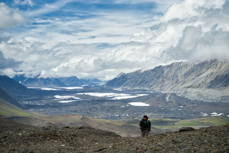 A man backpacking into a mountain pass with valley behind him