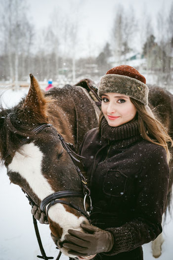 Animal Themes Cold Temperature Day Domestic Animals Horse Lifestyles Mammal Nature One Animal One Person Outdoors People Portrait Real People Snow Warm Clothing Weather Winter Young Adult
