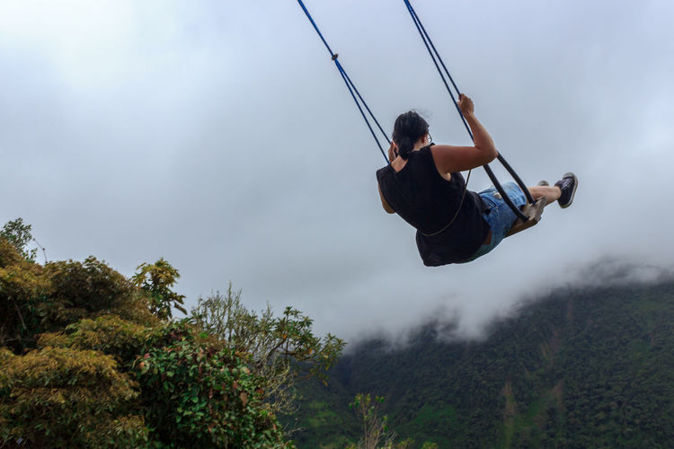 Rear view of woman playing on swing against sky