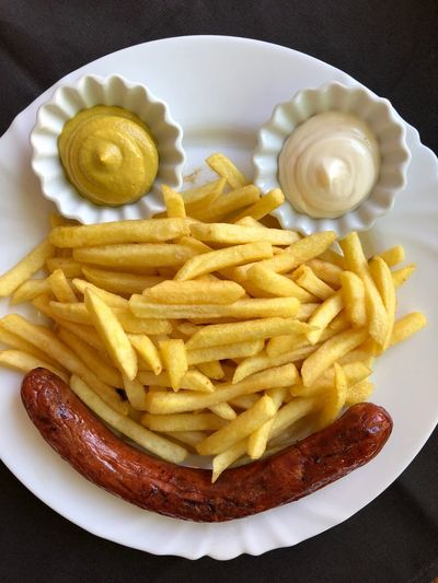 High angle view of french fries with dip and sausages arranged in plate on table
