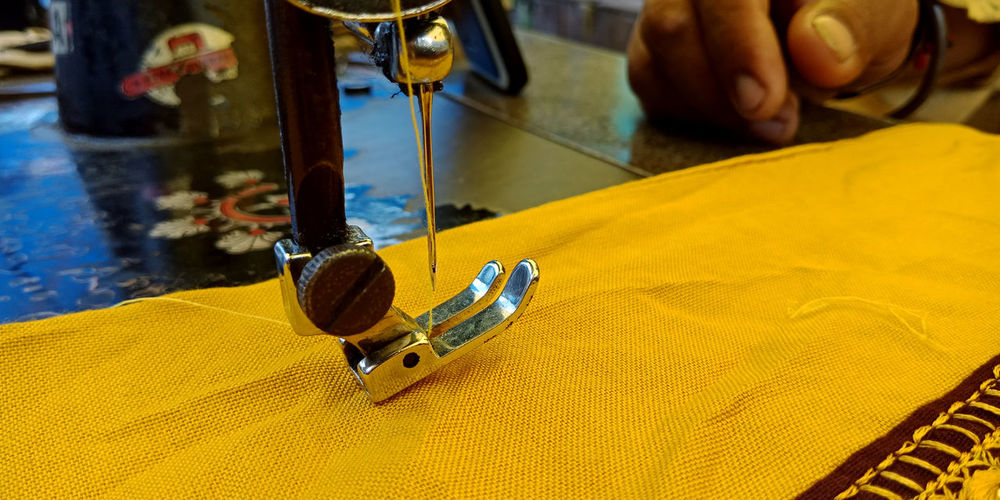 Cropped hand sewing yellow textile on machine