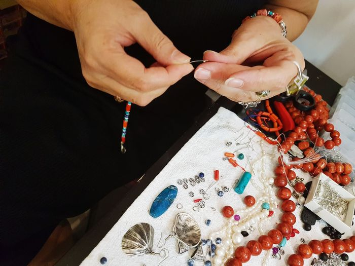 Midsection Of Woman Making Bead Necklace