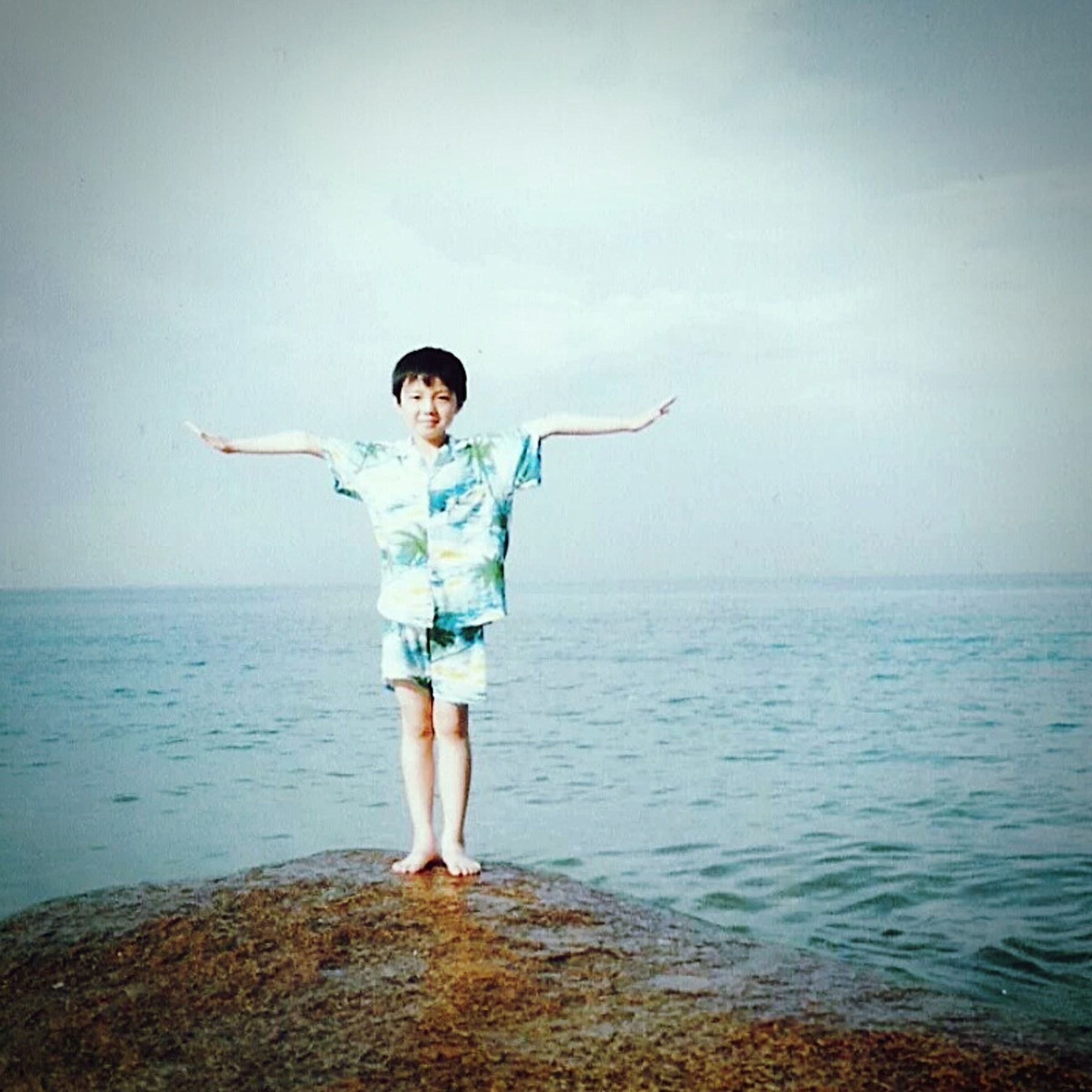 full length, water, lifestyles, casual clothing, leisure activity, sea, standing, person, sky, rear view, young adult, horizon over water, front view, arms outstretched, tranquility, nature, portrait, childhood
