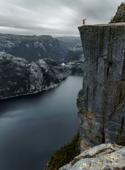 A girl is standing near the edge of the Pulpit Rock mountain - Preikestolen - above the Lysefjord in Rogaland near Stavanger, Norway. Dark Edge Of The World Matthias Church Norway Preikestolen Rock Stavanger Stavanger Norway Cliff Dengler Fjord Fjords Girl Mountain One Person Person Prekestolen Pulpit Rogaland Snapshopped