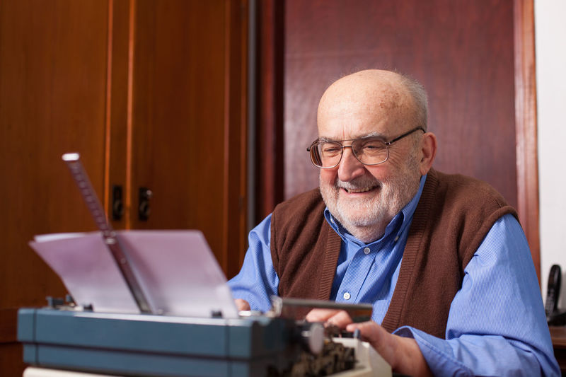 old man typing on a typewriter Author Caucasian Creativity Desk Document Elderly Eyeglasses  Happy Indoors  Letter Man Novel Old Paper People Retro Senior Men Sitting Smiling Story Typewriter Typing Vintage Work Writer