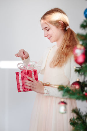 Happy girl unpacking Christmas gift standing behind a tree Box Child Childhood Christmas Christmastime Decorated Dress Enjoying Enjoyment Gift Girl Happiness Happy Holding Holiday Home Joy Lifestyles Pink Present Smile Tree Unwrapping Wrapped Young