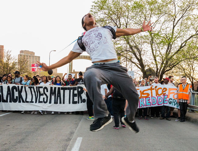 Man jumping with energy, during Blacklives matter protest. African American America Blacklivesmatter Blackman Casual Clothing City City Life Culture Day Full Length Issues Leisure Activity Lifestyles Marching Outdoors Police Protest Posters Racism Rally Sky Social Photography Tree