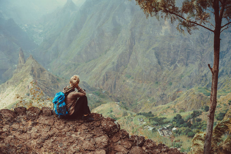 Female sitting in front of breathtaking panorama of deep lush ribeira surrounded by towering peaks. Verdant Xo-Xo valley on Santo Antao Island Cape Verde. Cape Verde Edge Activity Backpack Beauty In Nature Casual Clothing Cliff Day Full Length Leisure Activity Lifestyles Mountain Mountain Range Nature Non-urban Scene One Person Outdoors Plant Real People Rocks Scenics - Nature Sitting Tranquil Scene Tranquility Tree