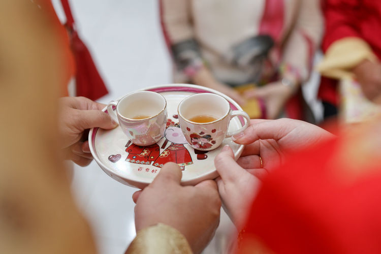 Chinese wedding couple holding tea cup during traditional tea ceremony Chinese Wedding Traditional Wedding Asian  Tea Ceremony Human Hand Women Togetherness Drink Holding Men Bride Close-up Wedding Ceremony Ceremony Bridegroom Newlywed Groom