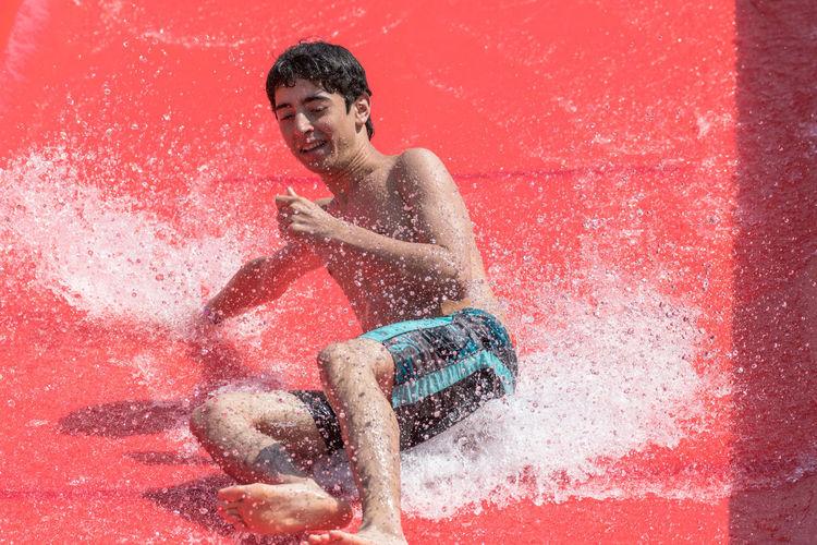 High angle view of young man enjoying water slide at park