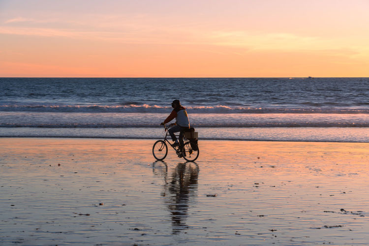 Man riding bicycle on beach against sky during sunset