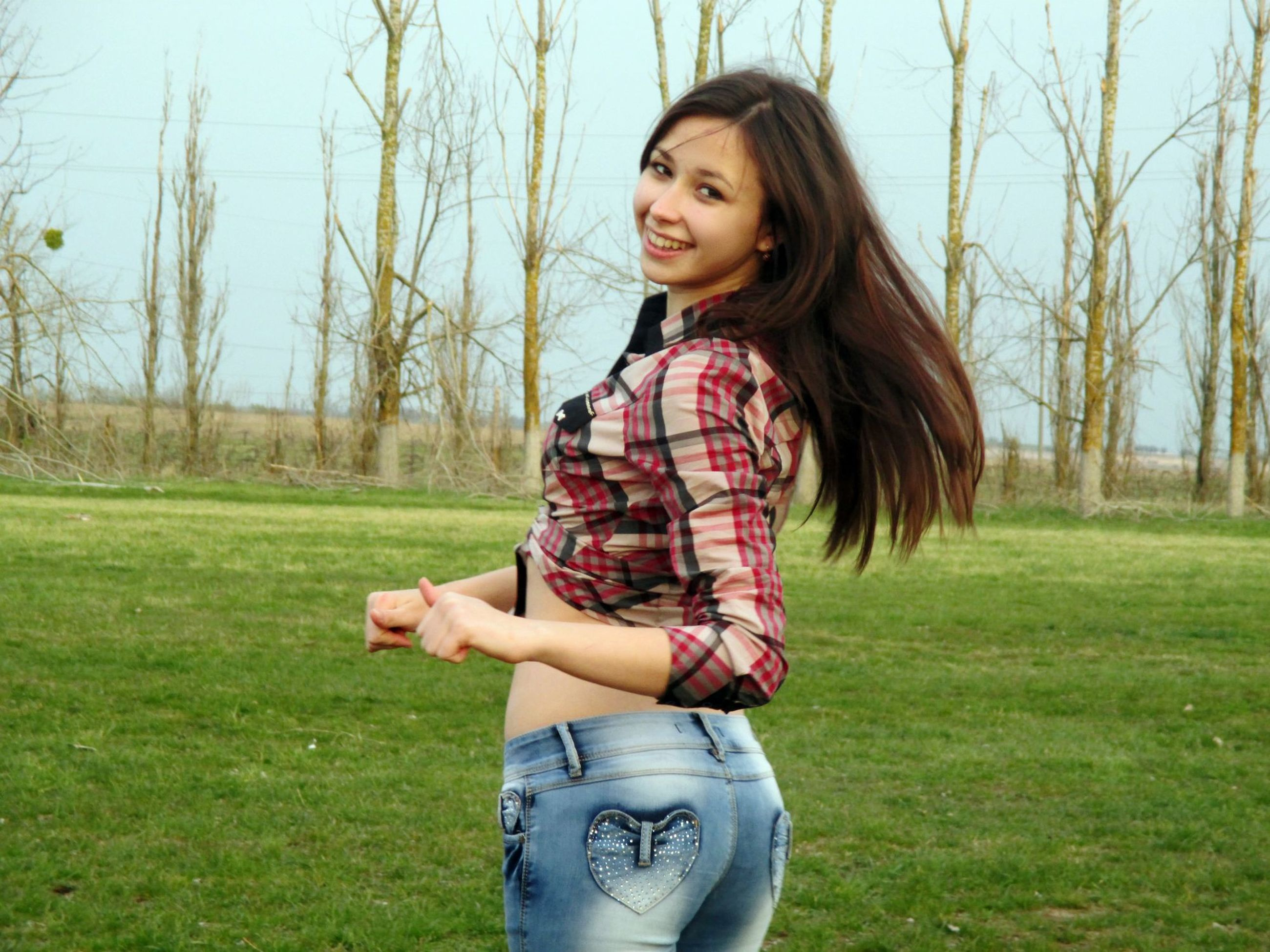 person, grass, young adult, casual clothing, lifestyles, young women, portrait, looking at camera, leisure activity, smiling, long hair, front view, grassy, three quarter length, standing, happiness, tree