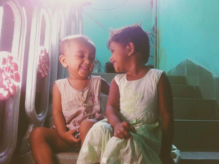 Smiling Siblings Sitting On Steps