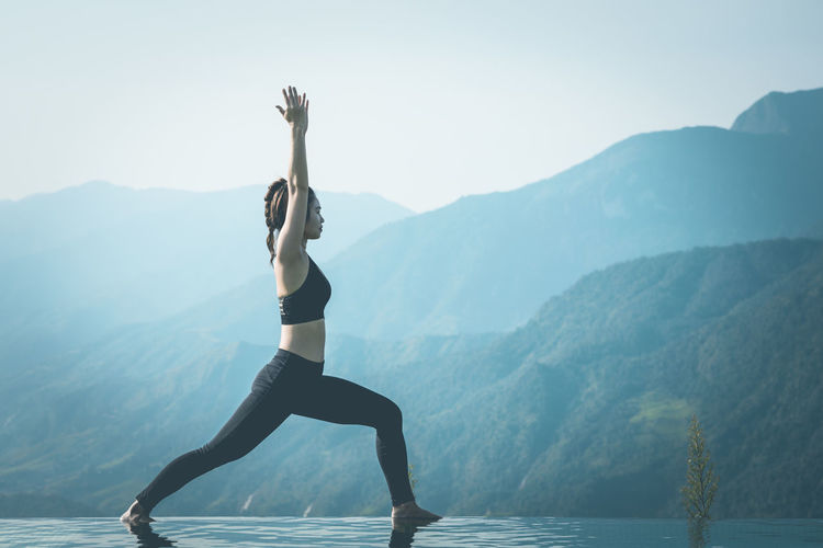 Side view of woman exercising on infinity pool against mountains