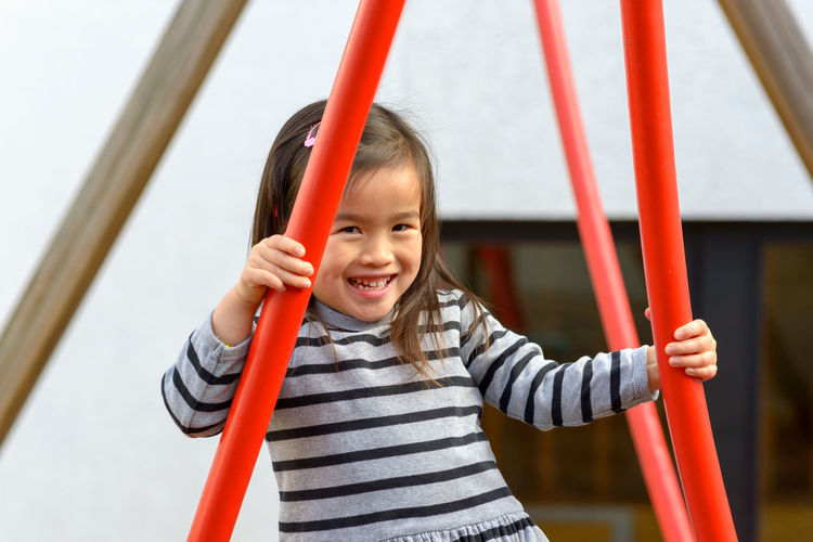 Portrait of happy girl standing on playground
