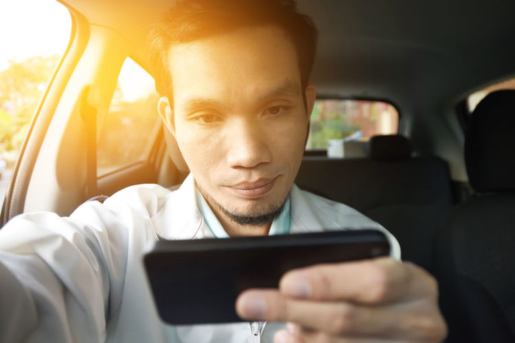 Mid adult man using mobile phone while sitting in car