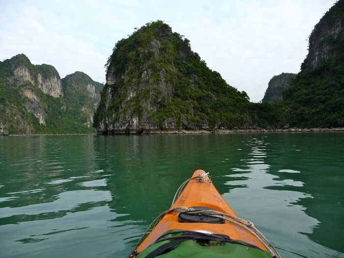 Cropped Image Of Canoe In Sea Against Mountains